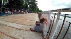 Street child sitting on lake boardwalk - stock footage