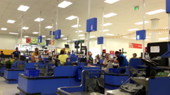 People paying foods at check out counter inside Walmart store - stock footage