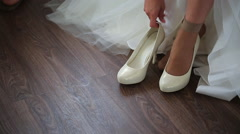 Fiancee puts on pair of white bridal shoes for going out - stock footage