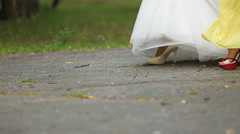 Fiancee and her bridesmaids pace on asphalt all together - stock footage