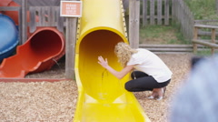 4K Happy little girls coming down slide at adventure playground Stock Footage