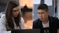 Brunette woman in glasses with a young asian male student with glasses sitting Stock Footage