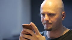 Bald bearded man chats in smartphone sitting in art studio Stock Footage