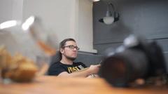 Bearded brunet sits on gray sofa in art studio Stock Footage