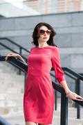 Alluring lady in red dress and sunglasses posing near the stairs outdoors - stock photo
