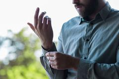 handsome young businessman buttoning up his shirt and sleeves - stock photo