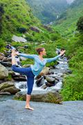 Woman doing yoga asana Natarajasana outdoors at waterfall Stock Photos