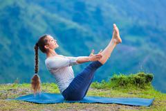 Woman doing Ashtanga Vinyasa Yoga asana Navasana - boat pose - stock photo