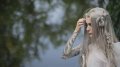 Beautiful model takes part in photo session on lake shore Stock Footage