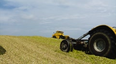 Five Yellow Tractors Tamp Silage in the Silo Trench Stock Footage
