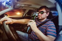 Man driving the car and drinking beer - stock photo