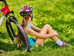 Bikes cycling girl wearing helmet sitting near bicycle. Stock Photos