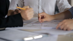 It is close-up image of people discussing blueprints and making corrections - stock footage