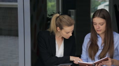 Two females are discussing business issues in office corridor Stock Footage
