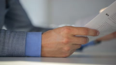 Male notary in suit jacket and light blue shirt holds a document and reads them Stock Footage