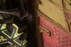 Horizontal close up of sole of worn running  shoe, positioned vertically, wit - stock photo