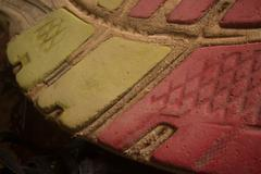 Horizontal ECU of sole of worn running shoe facing towards the frame perspect - stock photo