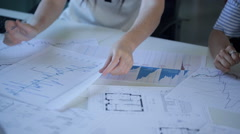 Table with graphs and blueprints apartment in real estate office, women's hands Stock Footage