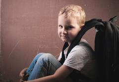 Little boy with a big black backpack, a guy with blond hair posing at a Stock Photos