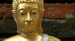 Close up Gold Buddha Face and aincient Brick Structure Stock Footage