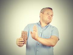 fat man refuses to chocolate. - stock photo
