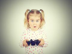 Little girl playing video games with gamepad in hands. Stock Photos