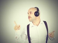 Mustache businessman listening to music on headphones and sings Stock Photos