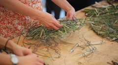 People stands near wooden table in art studio and create wreaths from grass Stock Footage