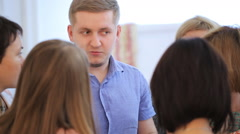 Blonde man stands in surrounding of group of women and answers their questions Stock Footage