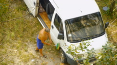 Man cleaning minibus with brush Stock Footage