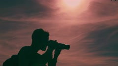 Young Photographer Backlight, Shooting at Sunset. Sun Reflection Stock Footage