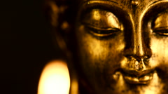Shallow focus closeup of rotating face of a golden candlelit Buddha figure Stock Footage
