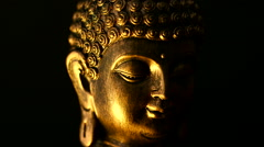 Rotating close up shot of golden peaceful Buddha face, against black background Stock Footage