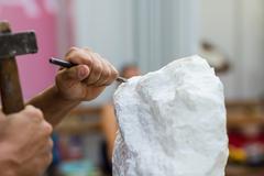 Man carving stone statue Stock Photos