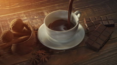 Cup of hot chocolate, cinnamon sticks, nuts and chocolate bar on wooden table Stock Footage