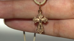 Golden Orthodox cross swinging on palm Stock Footage