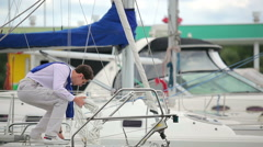 A guy throw coiled rope on the deck of the yacht Stock Footage
