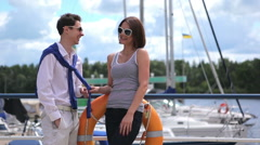 The girl are flirting with guy near the yacht club Stock Footage