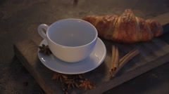 Pouring hot chocolate with croissants and cinnamon sticks on grunge table Stock Footage