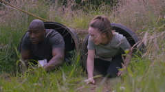 4K Competitors in assault course race climbing out of tunnel obstacles Stock Footage