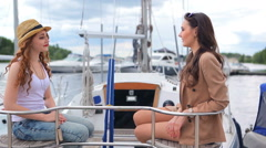 The girls sitting on the yacht and laughing Stock Footage