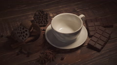 Pouring hot chocolate with anise and cinnamon sticks on dark wooden table Stock Footage