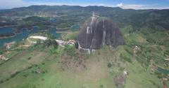Aerial wide shot circling around Piedra del Penol rock formation Stock Footage