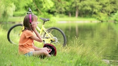 Little girl with headphones listening to music in summer park at lakeside Stock Footage