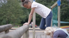 4K Little girls playing on climbing bars in adventure playground Stock Footage