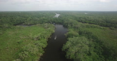 Aerial descent into a Belize River as a boat comes along Stock Footage