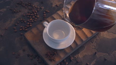Cup of black coffee and beans over grunge wooden table Stock Footage