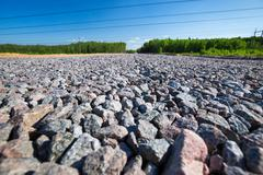 Unfinished asphalt country road in pine forest. Breakstone paving - stock photo