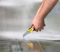Worker cutting polycarbonate with knife Stock Photos