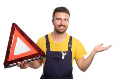 Confidence mechanic holding one car triangle in his hand isolated on white ba Stock Photos